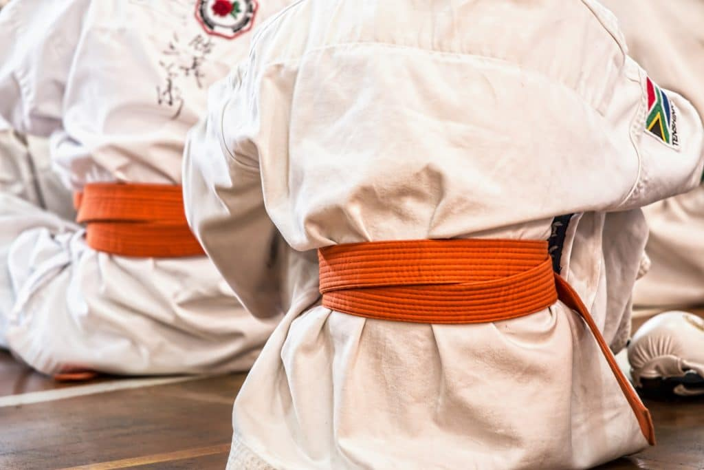 people wearing martial arts outfits and orange belts sitting on the floor
