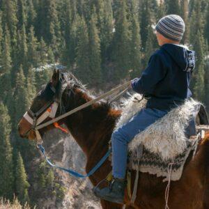 a child horse riding outdoors, a sunnah academy of sports horse riding course